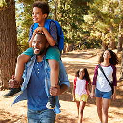 family walking through the woods with son on dad's back